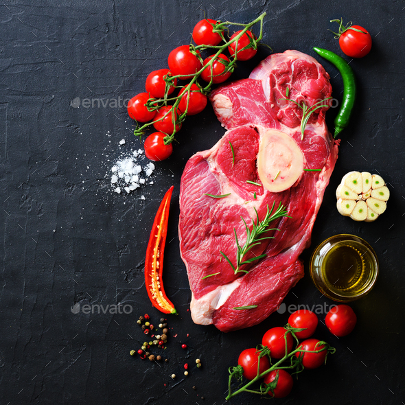 Raw fresh meat steak with cherry tomatoes, hot pepper, garlic, oil and herbs on dark stone, concrete - Stock Photo - Images