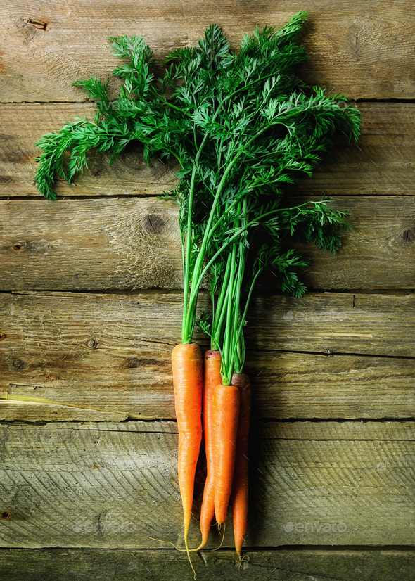 Bunch of fresh organic carrots on a wooden background with sunlights. Concept of diet, raw - Stock Photo - Images
