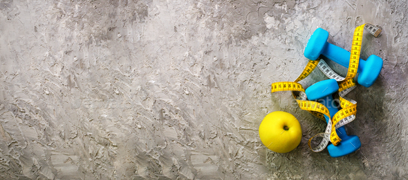 Turquoise dumbbells with measuring tape and yellow apple on concrete background. Free space for your - Stock Photo - Images