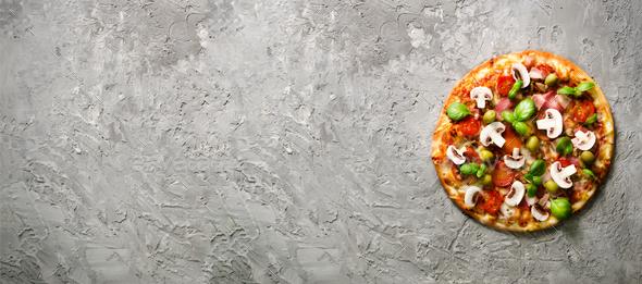 Fresh italian pizza with mushrooms, ham, tomatoes, cheese, olive, basil on grey concrete background - Stock Photo - Images