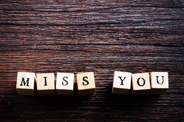 Heart shaped chewing candies and words miss you on cubes, wooden background. Free space for your - Stock Photo - Images