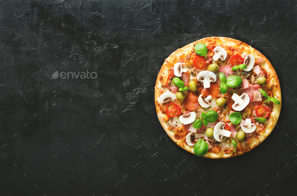 Fresh italian pizza with mushrooms, ham, tomatoes, cheese, olive, basil on black concrete background - Stock Photo - Images