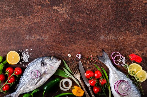 Dorada, fresh fish with vegetable, lemon, herbs, onion, paprika, cherry tomatoes, onion, salt - Stock Photo - Images