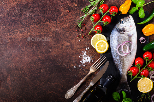 Dorada, fresh fish with vegetable, lemon, herbs, onion, paprika, cherry tomatoes, onion, salton dark - Stock Photo - Images
