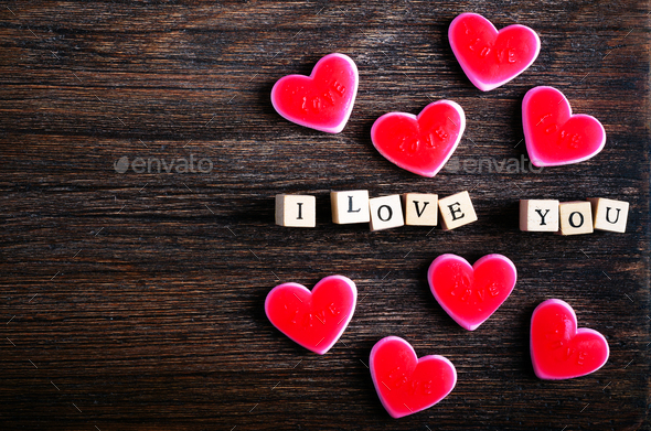 Heart shaped chewing candies and words I love you on cubes, wooden background. Free space for your - Stock Photo - Images