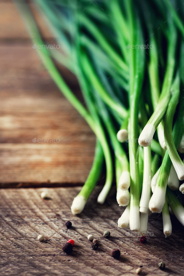 Bunch of fresh organic green onions, scallions on wooden background with pepper. Copyspace - Stock Photo - Images
