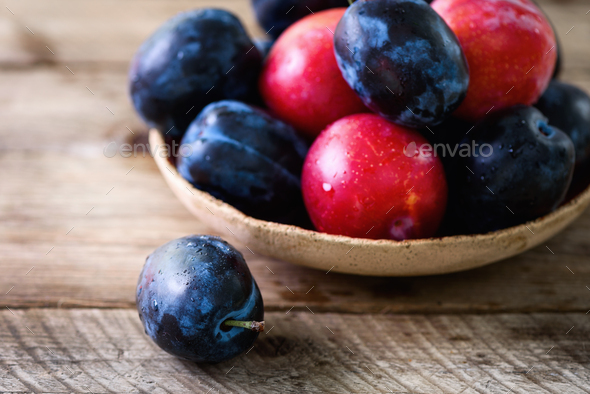 Blue and pink organic plums on dark wooden background. Copyspace - Stock Photo - Images