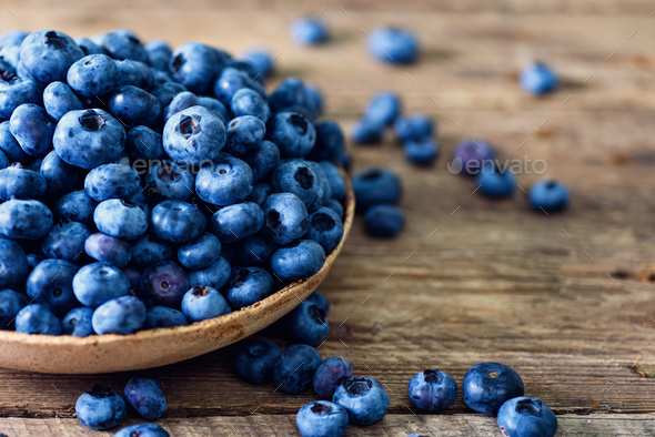 Blueberries on wooden table. Blueberry bowl on vintage background with copyspace. Berries frame - Stock Photo - Images