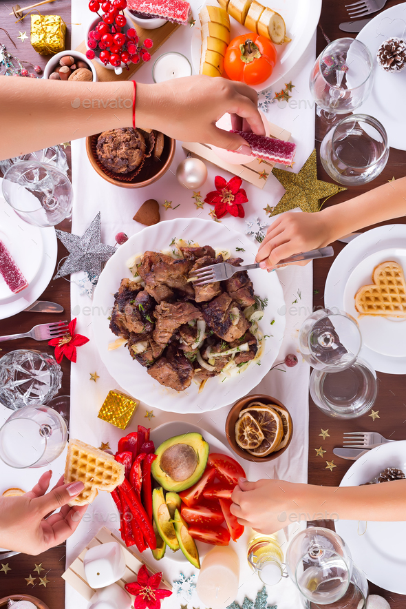 Christmas table setting with food on a plate, mom and child hands handing food and decoration on - Stock Photo - Images