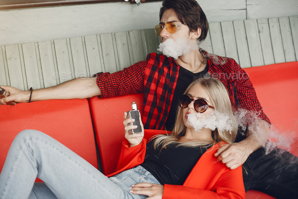 Stylish young couple with vape in a city - Stock Photo - Images