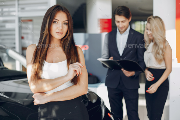 Stylish and elegant people in a car salon - Stock Photo - Images