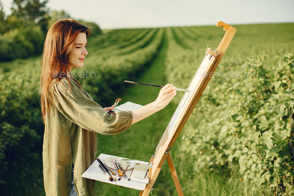 Elegant and beautiful girl painting in a field - Stock Photo - Images