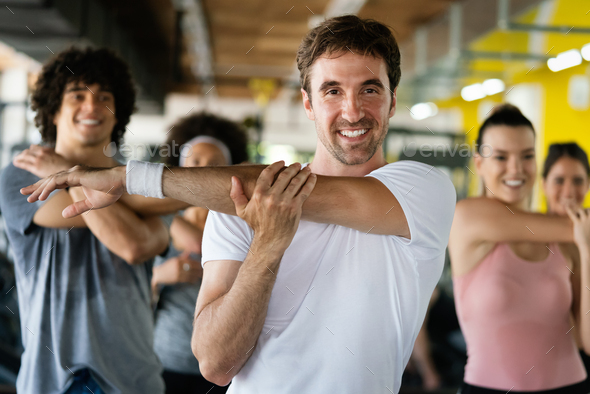 Beautiful fit people exercising together in gym - Stock Photo - Images