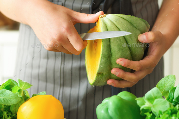 Woman peeling pumpking, vegetables, onion, tomatoes, corn, bell pepper, spinach, lettuce leaves - Stock Photo - Images