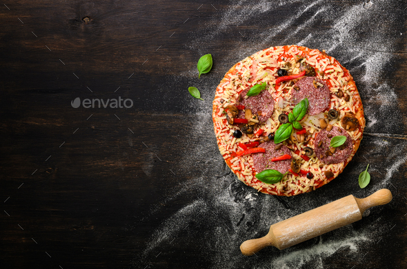 Pizza woth basil, rolling pin, flour on dark black background, copy space, top view - Stock Photo - Images