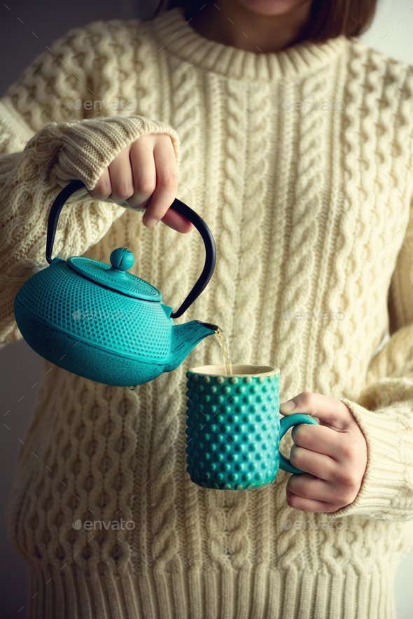 Woman in warm knitted woolen sweater holds turquoise teapot and pouring herbal tea into handmade cup - Stock Photo - Images