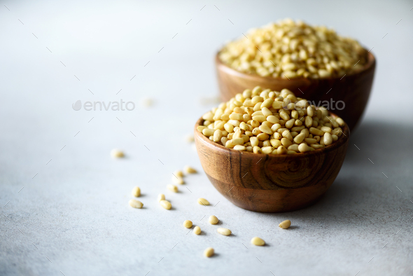 Shelled organic pine nuts in wooden bowl. Nuts background. Top view, copy space - Stock Photo - Images
