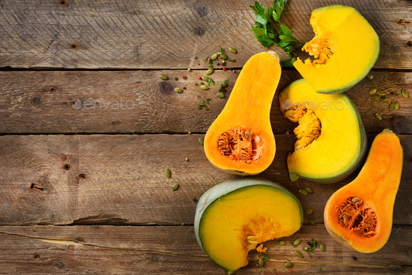 Cut ripe orange pumpkin with seeds and herbs on rustic wooden background. Vegetarian and raw organic - Stock Photo - Images