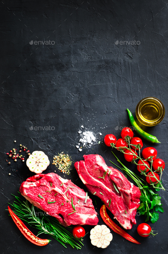 Raw meat, beef steak on a stone cutting board with rosemary, spices, salt, oil, cherry tomatoes, hot - Stock Photo - Images
