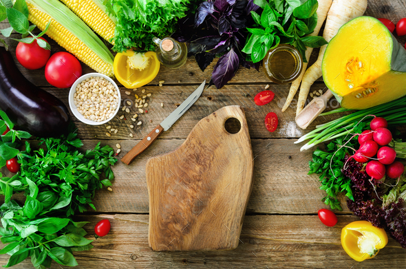 Vegetables on wooden background. Herbs, basil, onion, pumpkin, pine nuts, tomatoes, corn, radish - Stock Photo - Images