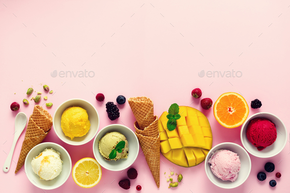 Ice cream balls in bowls, waffle cones, berries, orange, mango, pistachio on pink shabby chic - Stock Photo - Images