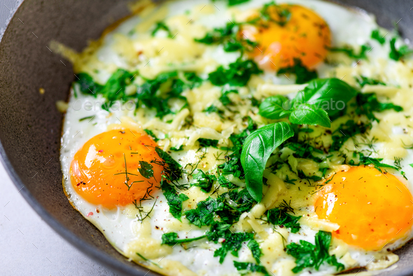 Three fried eggs with peppers, herbs, cheese in pan, closeup, macro - Stock Photo - Images