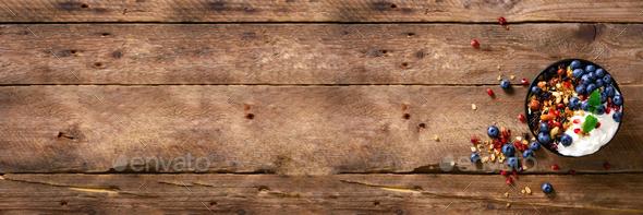 Tasty homemade granola, yogurt, fresh organic berries, pomegranate, mint on rustic wooden background - Stock Photo - Images