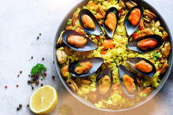 Traditional spanish seafood paella in pan rice, peas, shrimps, mussels, squid on light grey concrete - Stock Photo - Images
