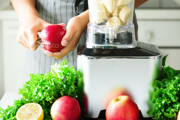 Woman hands cutting, chopping apple for green smoothie. Homemade healthy green smoothie. White - Stock Photo - Images