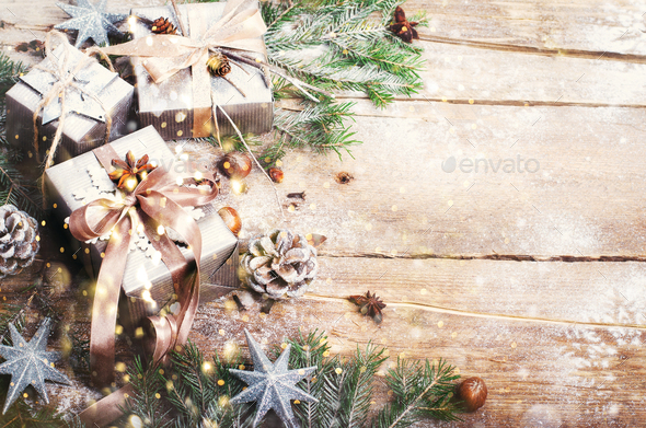 Gift boxes on old wooden background with silver stars, cones, hazelnut, anise, tape, ribbon - Stock Photo - Images
