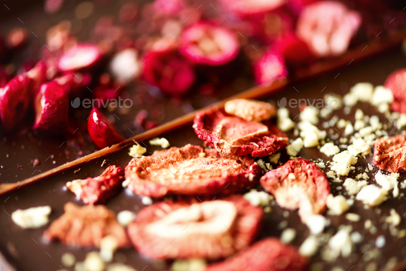 Handmade chocolate bars with dried cranberries, raspberries and pistachios, strawberries, nuts. Dark - Stock Photo - Images