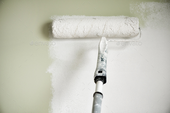Hand painting wall with paint roller, pastel color. Appartment renovation, repair, building and home - Stock Photo - Images