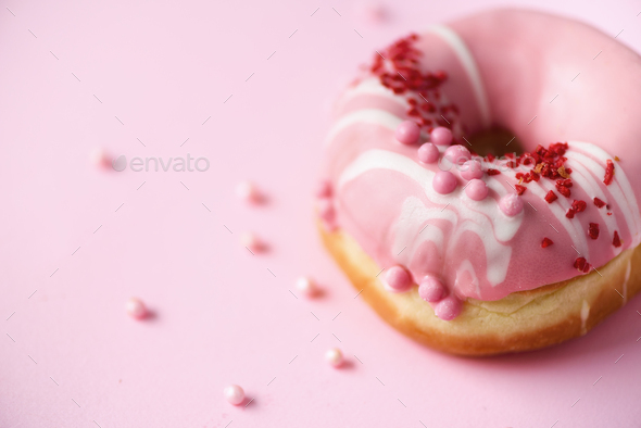 Sweet doughnut with pink icing on pastel background. Tasty donut on pink texture, copy space, top - Stock Photo - Images
