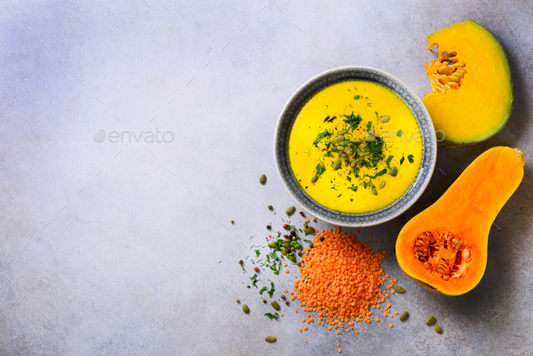 Vegetable and lentils creamy soup, cut pumpkin, seeds, parsley on light grey background. Top view - Stock Photo - Images