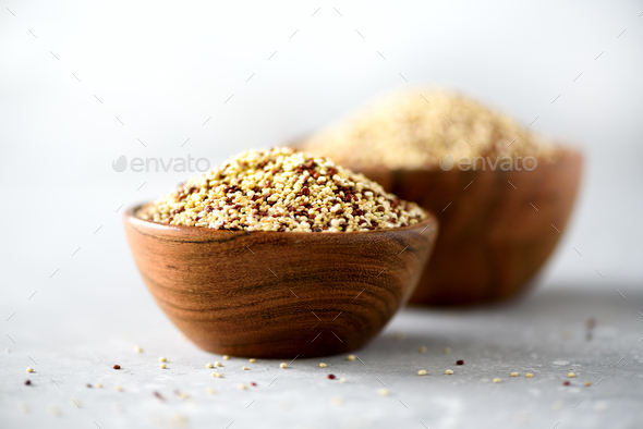 White and red raw organic quinoa in wooden bowl and rosemary on grey background. Healthy food - Stock Photo - Images