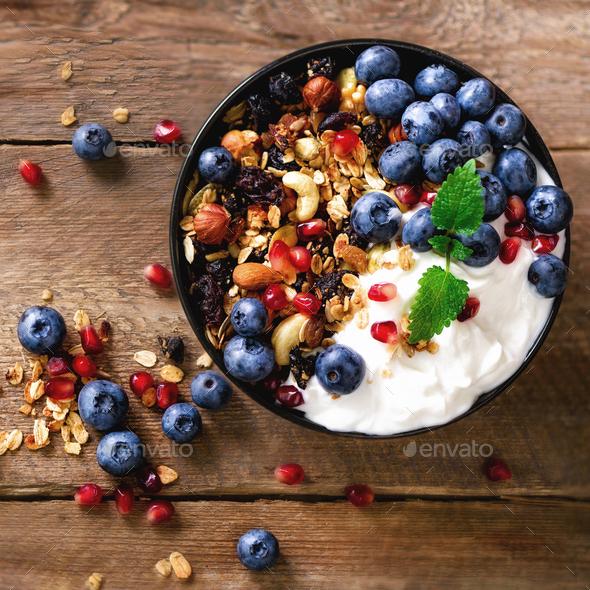Tasty homemade granola, yogurt, fresh organic berries, pomegranate, mint on grey concrete background - Stock Photo - Images
