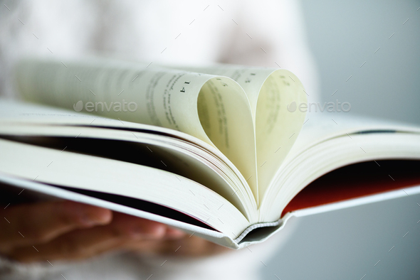 Book with opened pages and shape of heart in girl hands. Copy space. Love concept - Stock Photo - Images