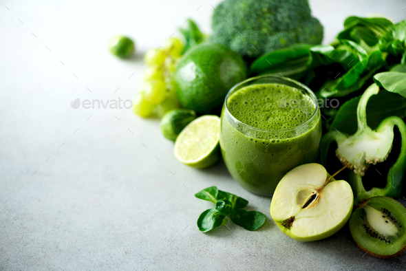 Glass with green health smoothie, kale leaves, lime, apple, kiwi, grapes, banana, avocado, lettuce - Stock Photo - Images