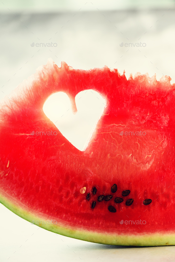 Piece of watermelon with heart shape on grey concrete background. Copy space. Flat lay. Greeting - Stock Photo - Images