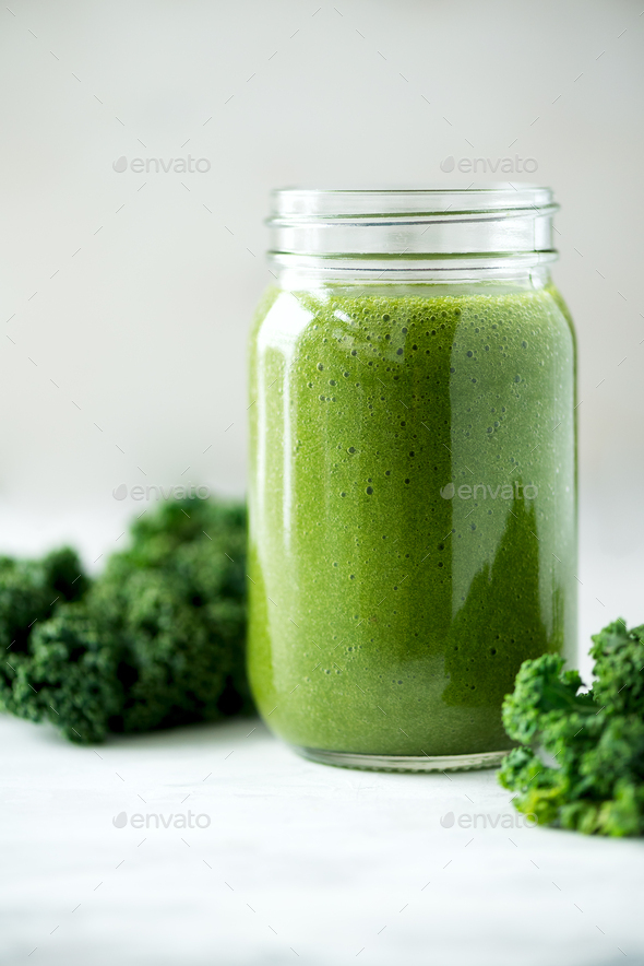 Glass jar mugs with green health smoothie, kale leaves, lime, apple, kiwi, grapes, banana, avocado - Stock Photo - Images
