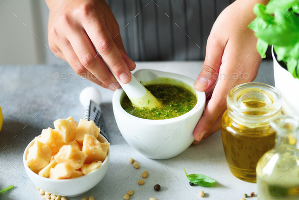 Woman hands making italian pesto in bowl. Ingredients - basil, lemon, parmesan, pine nuts, garlic - Stock Photo - Images
