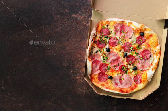 Fresh pizza in delivery box on dark concrete background. Top view, copy space - Stock Photo - Images
