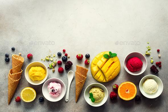 Ice cream balls in bowls, waffle cones, berries, orange, mango, pistachio on grey concrete - Stock Photo - Images