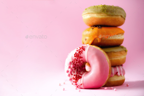 Stack of glazed colorful assorted donuts with sprinkles on pink background. Copy space. Sweet - Stock Photo - Images