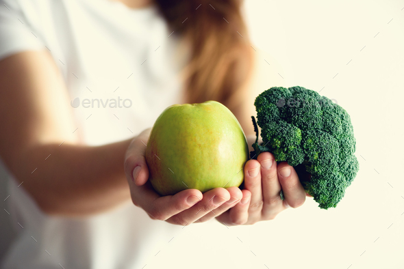 Woman in white T-shirt holding geen apple and broccoli in her hands. Copy space. Clean detox eating - Stock Photo - Images