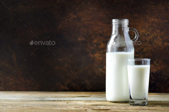 Milk bottle and glass on wooden table, dark background. Healthy eating concept. Copy space - Stock Photo - Images