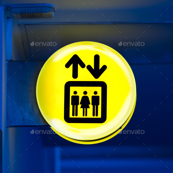Bright yellow lift or elevator symbol, sign on blue wall background with neon light. Copy space - Stock Photo - Images