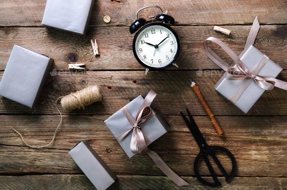 Gift boxes, black alarm clock, pen, scissors on wooden background. Preparing for birthday, christmas - Stock Photo - Images