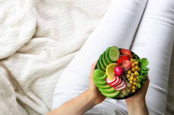 Girl holds in hands vegan, detox raw buddha bowl with avocado, quinoa, cucumber, radish, salad - Stock Photo - Images