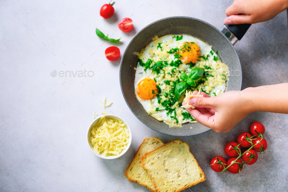 Girl hands above frying pan with three cooked eggs, herbs, cheese, tomatoes. Woman is making - Stock Photo - Images